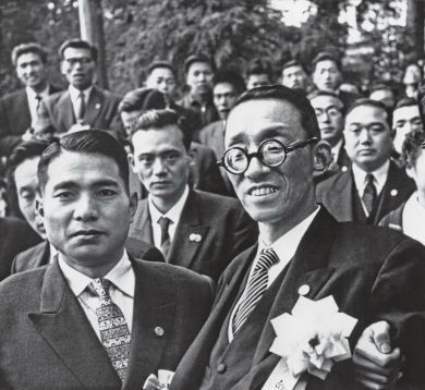 Close-cropped image of Ikeda and Toda facing the camera at the front of a group of men