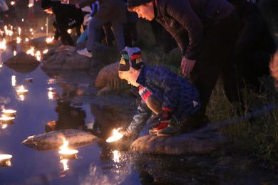 A woman and a child float a candle from the lake's shore at night