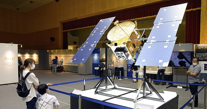 Exhibition visitors view a replica of a satellite.