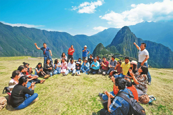 A group of people sitting in a circle on an open mountain top