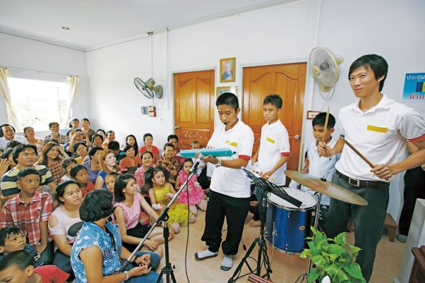 Four young people perform on musical instruments in a small room crowded with attentive listeners seated on the floor